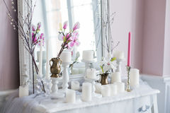 Sjaskig stilhemdesign Härlig garneringtabell med stearinljus, blommor framme av en spegel Arkivbilder