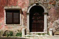 Sjaskig vägg av byggnaden med en rödbrun dörr och fönstret med slutare i Porec, Kroatien arkivbilder