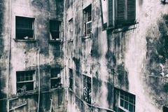 Sjaskiga väggar och fönster av en bostads- byggnad Arkivfoto