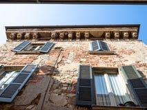 sjaskigt medeltida tegelstenhus på den gamla smala gatan royaltyfria bilder