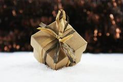 Sjofele elegante die Kerstmisgift in sneeuw wordt genesteld Stock Afbeeldingen