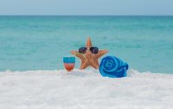 Sjöstjärna, handduk och coctail på den tropiska stranden för vit sand Royaltyfri Fotografi