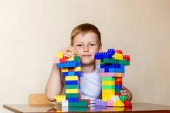 Sju-år-gammalt barn i en vit t-skjorta och plast- barns formgivare royaltyfria bilder