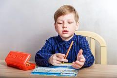 Sju åriga pojkeattraktioner i färgläggningen på skrivbordet, första-väghyvel royaltyfria bilder