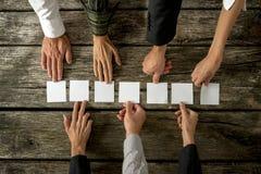 Sju händer av affärsfolk som förlägger sju vita kort i ett r Royaltyfri Bild