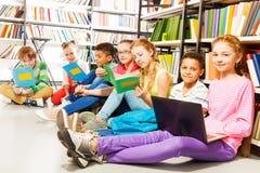 Sju le barn som i rad sitter på golv Arkivfoton