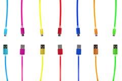 Sju mång--färgade usb-kablar, med kontaktdon under microen, de olika sluten av kabeln som pekar in mot de, på a Arkivfoto