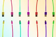 Sju mång--färgade usb-kablar, med kontaktdon under microen, de olika sluten av kabeln som pekar in mot de, på a Royaltyfria Foton