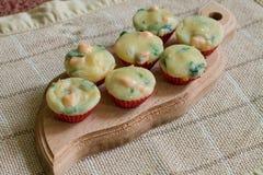 Sju muffin på den wood skärbrädan Royaltyfri Foto