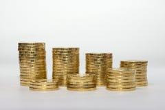 Sju myntkolonner monterade i rader som visar besparingtillväxt Royaltyfri Fotografi
