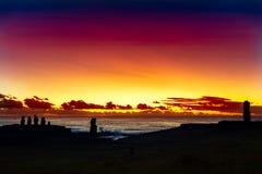 Sju stående moais på den röda och guld- solnedgången Arkivbild