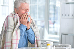 Sjuk äldre man med preventivpillerar royaltyfri fotografi