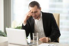 Sjuk affärsman som har den stränga huvudvärken, hållande smärtstillande medelreme Royaltyfria Foton