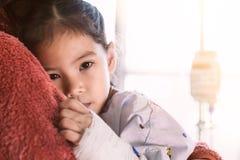 Sjuk asiatisk barnflicka som har dropplösningen som kramar hennes moder royaltyfri bild