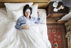 Sjuk asiatisk kvinna med feber som sover på sängen royaltyfri foto