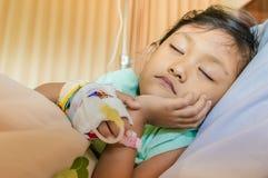 Sjuk asiatisk liten flickapatient som sover i sjukhus Arkivbild