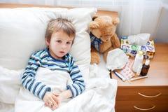 Sjuk barnpojke som ligger i säng med en feber som vilar royaltyfri fotografi