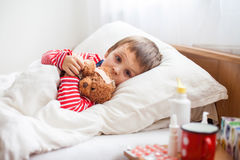 Sjuk barnpojke som ligger i säng med en feber som vilar arkivbilder
