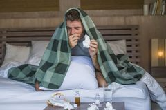 Sjuk för slösad och utmattad säng för man som förkylning och influensa för känsla hemma liggande opasslig lida nyser näsan med si fotografering för bildbyråer