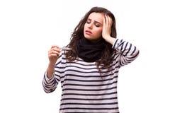 Sjuk flicka med en termometer på en vit bakgrund, isolat, influensa, förkylningar Arkivfoto