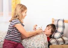 Sjuk flicka med hennes broder Arkivfoton