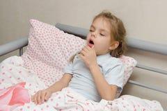 Sjuk flicka som ligger, i att hosta för säng Arkivbilder