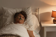 Sjuk hög kvinna i säng royaltyfria foton