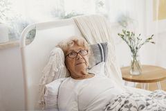 Sjuk hög kvinna med exponeringsglas som ligger i en säng royaltyfri fotografi