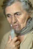 Sjuk hög kvinna med inhalatorn Fotografering för Bildbyråer