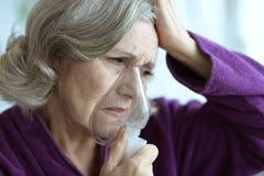 Sjuk hög kvinna med inhalatorn Royaltyfri Bild