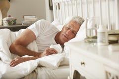 Sjuk hög man i säng hemma Royaltyfri Fotografi