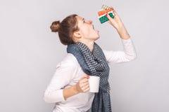 Sjuk innehavkopp för ung kvinna med te, många preventivpillerar, antibiotikummar royaltyfria foton