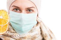 Sjuk kall kvinna som visar två orange skivor Arkivfoto