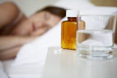 Sjuk kvinna i säng vid preventivpillerar på nattduksbordet Fotografering för Bildbyråer