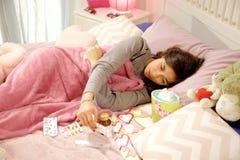 Sjuk kvinna i sängblickmedicin som avgör vilket för att ta Arkivbild