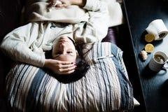 Sjuk kvinna i säng som kallar i sjukt, fridag från arbete Termometer som kontrollerar temperaturen för feber Royaltyfri Bild