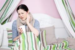 Sjuk kvinna med att vila för temperatur Arkivbild
