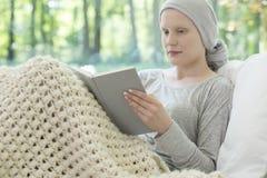 Sjuk kvinna med cancer som läser en bok på en soffa i klosterhärbärgen arkivbilder