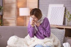 Sjuk kvinna med hostalidande från förkylning på soffan Royaltyfri Foto