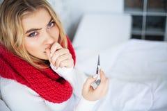 Sjuk kvinna med influensa Kvinnalidande från kallt ligga i säng med arkivfoto