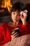 Sjuk kvinna med kallt vila på sofaen Fotografering för Bildbyråer