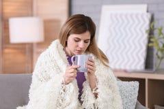 Sjuk kvinna med koppen av varmt drinklidande från förkylning Arkivbilder