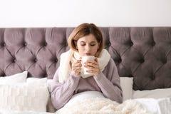 Sjuk kvinna med koppen av varmt drinklidande från förkylning Royaltyfri Fotografi