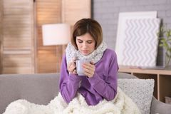 Sjuk kvinna med koppen av varmt drinklidande från förkylning Fotografering för Bildbyråer