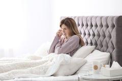 Sjuk kvinna med silkespapperlidande från förkylning i säng Royaltyfria Foton