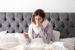 Sjuk kvinna med silkespappret och termometern Royaltyfri Foto