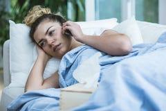 Sjuk kvinna med telefonen Royaltyfri Foto