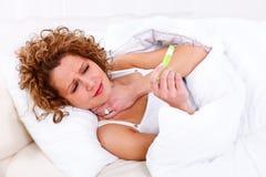 Sjuk kvinna med termometern royaltyfria foton