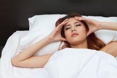 Sjuk kvinna på säng som masserar hennes huvud royaltyfri foto