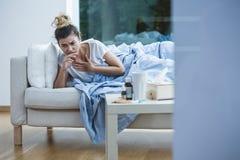 Sjuk kvinna på soffan arkivfoto